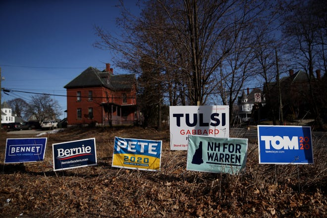 Yard signs for Democratic presidential candidates are posted in front of a home on Feb. 5, 2020, in Manchester, New Hampshire. The New Hampshire primary is Feb. 11.