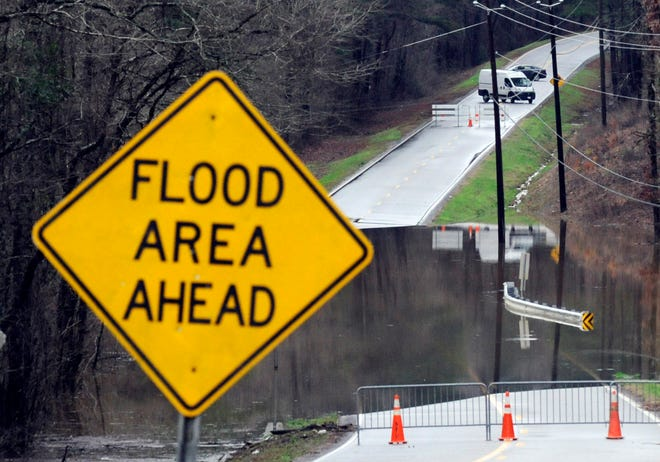 Vehicles turn around on a road blocked by floodwaters in Helena, Ala., on Feb. 11. The National Weather Service says flooding is expected from central Mississippi to north Georgia after downpours, and severe storms could follow the rain.