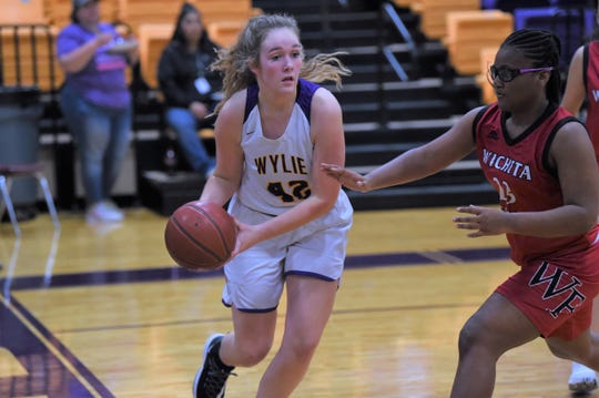 Wylie's Bailey Roberts (42) looks to make a pass along the baseline against Wichita Falls High at Bulldog Gym on Tuesday, Feb. 11, 2020. Roberts scored a game-high 16 points in the 57-27 win for a share of the District 4-5A title.