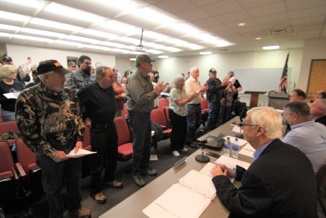 """Attendees at the Madison County Board of Commissioners cheer the passage of a resolution declaring the county a """"Second Amendment Sanctuary."""""""