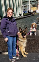 """From left: Mary Cummings, her German Shepherd, Ivan, and Beagle, Halo, pose in Rockefeller Center in New York City before heading to a taping of an episode of """"The Tonight Show with Jimmy Fallon."""""""