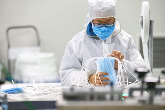A worker produces protective face masks at a factory in Qingdao in China's eastern Shandong province, on February 6, 2020, to support the supply of medical materials during a virus outbreak that originated from Hubei's provincial capital city of Wuhan. - The number of confirmed infections in China's coronavirus outbreak has reached 28,018 nationwide with 3,694 new cases reported, the National Health Commission said on February 6. (Photo by STR / AFP) / China OUT (Photo by STR/AFP via Getty Images)