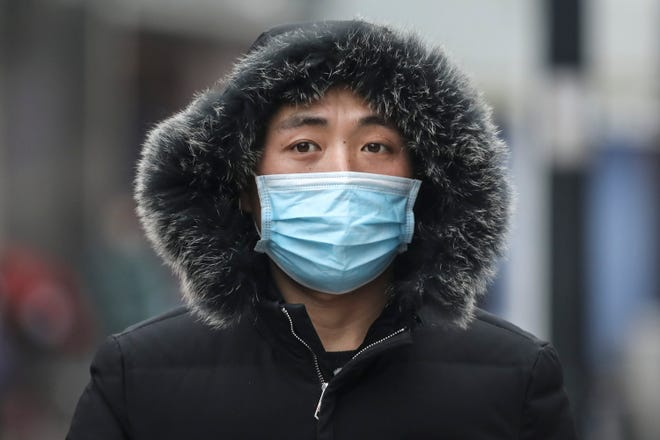 """WUHAN, CHINA - JANUARY 22:  (CHINA OUT) A man wears a mask while walking in the street on January 22, 2020 in Wuhan, Hubei province, China. A new infectious coronavirus known as """"2019-nCoV"""" was discovered in Wuhan as the number of cases rose to over 400 in mainland China. Health officials stepped up efforts to contain the spread of the pneumonia-like disease which medicals experts confirmed can be passed from human to human. The death toll has reached 17 people as the Wuhan government issued regulations today that residents must wear masks in public places. Cases have been reported in other countries including the United States, Thailand, Japan, Taiwan, and South Korea.  (Photo by Getty Images)"""