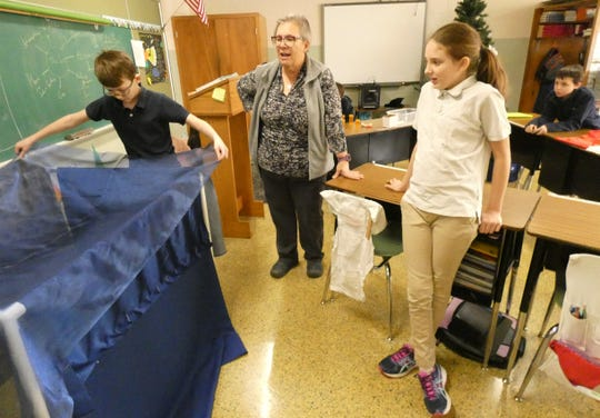 Joe Rader, right, demonstrates how his project to help a multi-handicapped class at Buckeye Central schools will look when it's finished while teacher Mary Obringer and classmate Madison Aldred watch Tuesday at St. Bernard's School in New Washington.