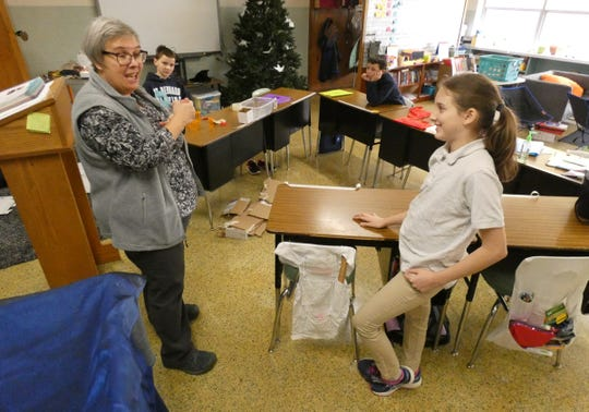 Teacher Mary Obringer, left,  discusses her class' projects designed to help a multi-handicapped class at Buckeye Central schools Tuesday at St. Bernard's School in New Washington. Student Madison Aldred, right, listens.