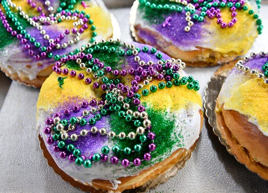 A finished Mardi Gras King Cake on display at JB Bakery in Burlington on Wednesday, Feb. 12, 2020. A small plastic baby Jesus is placed on top the decorated dessert bread for the customer to insert inside. Tradition calls for the recipient of that slice to buy the next cake.