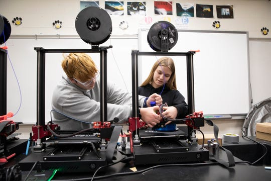Paint Valley sophomore Kenton Chamberlin, left, and junior Merle Polzer load film into a third generation 3-D printer during their 3D Print and Design class with Marc Miller on Feb. 11, 2020.