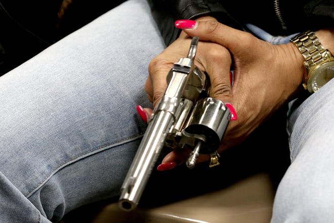 A woman holds an unloaded revolver during a concealed carry weapon (CCW) class in the Cincinnati area last month.