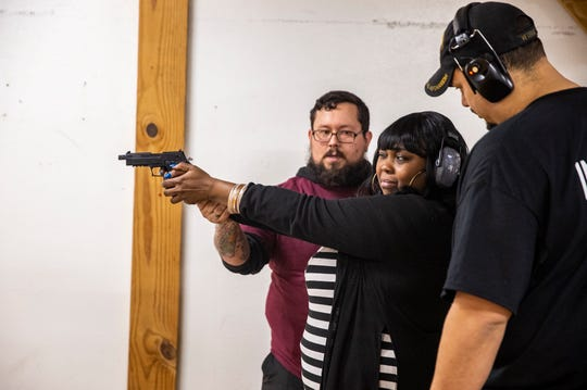 Kai Brown of Bond Hill gets instruction on how to hold a gun from Timm Penrod and Henry Ware, right, with Arm the Populace during an all-female concealed carry and weapons class at New Prospect Baptist Church Saturday, February 8, 2020.