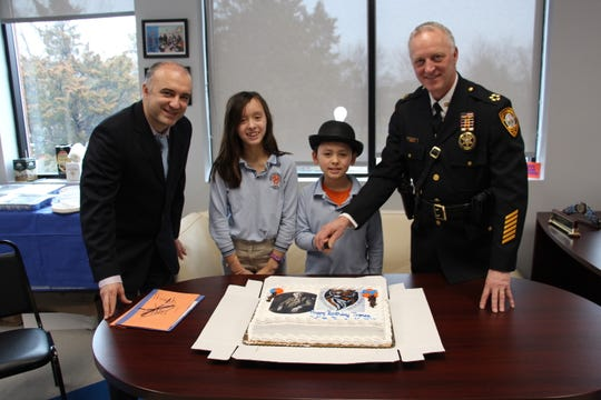 Sheriff Darrin Russo and two students, who are seventh generation descendants of Thomas Edison, cut the cake for all to enjoy.