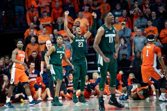 Michigan State Spartans forward Xavier Tillman (23) celebrates with guard Cassius Winston (5) and forward Aaron Henry (11) after the second half as Illinois Fighting Illini guard Ayo Dosunmu (right bottom) lays on the floor at State Farm Center on Feb. 11, 2020.