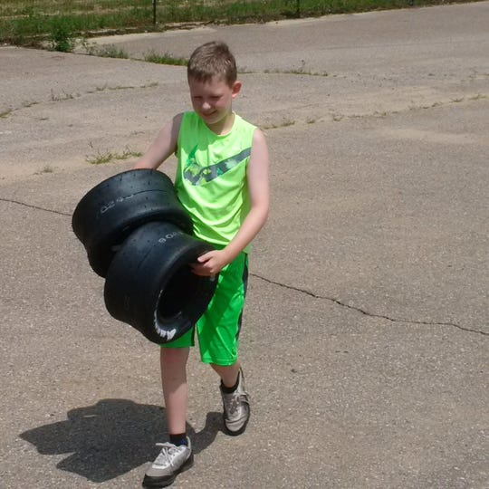 Keegan Sobilo carries racing tires before practice at M40 Speedway in Jones, Michigan on July 28, 2018.