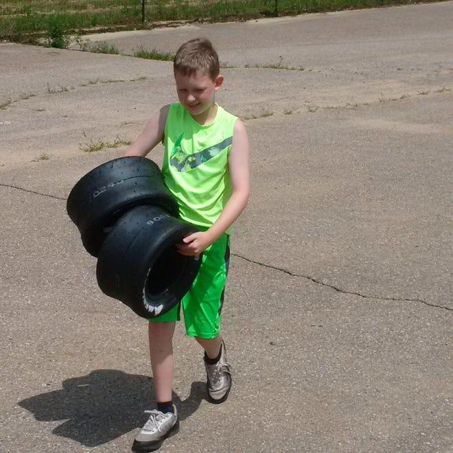 Keegan Sobilo carries racing tires on July 29, 2018.