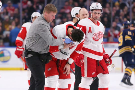 Detroit Red Wings forward Brendan Perlini (29) is helped off the ice by trainer and forward Dylan Larkin (71) during the first period of an NHL hockey game against the Buffalo Sabres, Tuesday, Feb. 11, 2020, in Buffalo, N.Y.