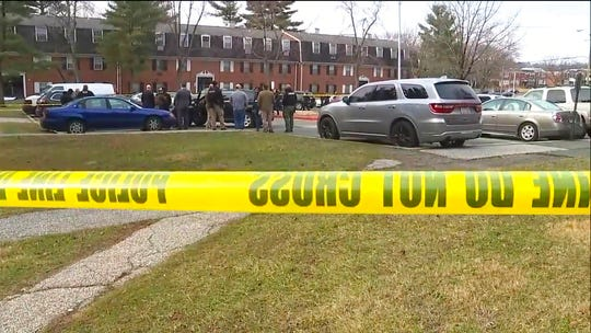 This image provided by WMAR-2 News shows emergency and law enforcement officials responding to the scene of a shooting,  Wednesday, Feb. 12, 2020 in Baltimore.  Two law enforcement officers with a fugitive task force were injured and a suspect died in a shooting on Wednesday, the U.S. Marshals Service said.
