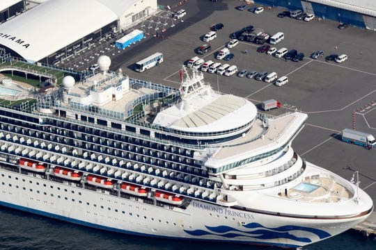 The U.S.-operated Diamond Princess is anchored as emergency vehicles stand by at Yokohama Port, near Tokyo, Wednesday, Feb. 12, 2020. Japan's Health Ministry said Wednesday that 39 new cases of a virus have been confirmed on the cruise ship quarantined at the Japanese port.