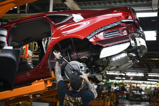 An assembly line worker at the General Motors Detroit-Hamtramck plant uses a torque wrench on a Chevrolet Impala as the plant will be converting from internal-combustion production to EV.