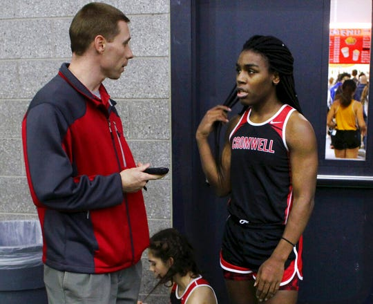 In this Feb. 7, 2019 file photo, Cromwell High School track coach Brian Calhoun, left, speaks to transgender athlete Andraya Yearwood during a break at a meet at Hillhouse High School in New Haven, Conn.