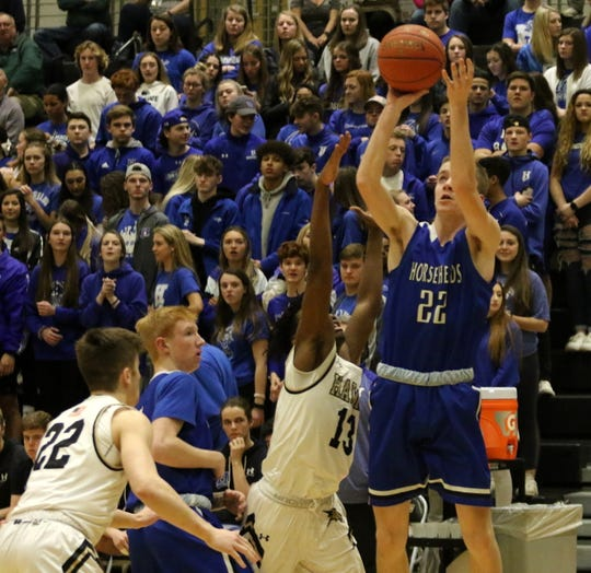 Andrew McLaughlin of Horseheads puts up a shot as Corning's Nesu Maphosa (13) defends during the Blue Raiders'75-64 win in boys basketball Feb. 11, 2020 at Corning-Painted Post High School.