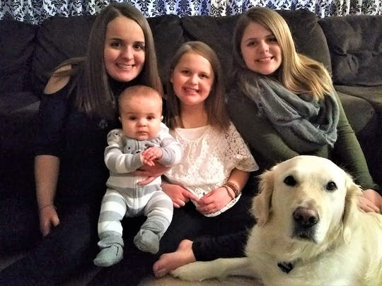 Buddy, the service dog, helps the Westphal children of Fond du Lac by alerting to complications they suffer from a rare condition, congenital adrenal hyperplasia. From left are: Emma, 14, Grayson, 6 months,  Olivia, 9, and Chloe, 12 1/2.