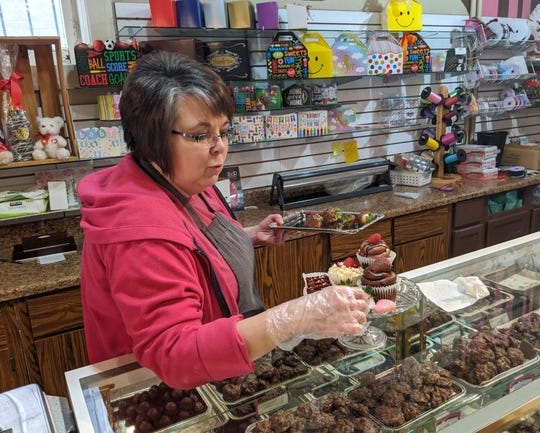 Donna McNemar builds a plate of treats at Coco Beans Candy Cupcakes and More in preparation for Valentine's Day.