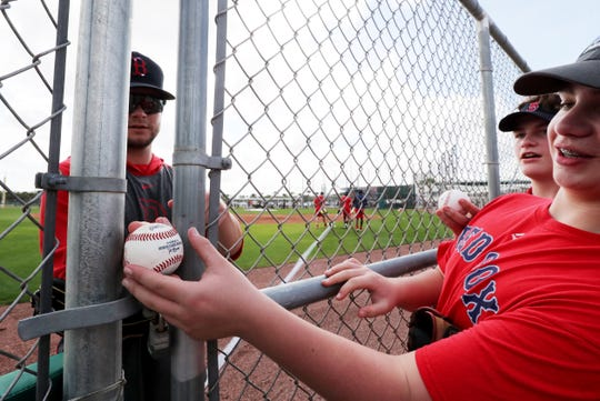 Sam Bernard, 14 of Massachusetts, gets his ball back through a wide opening in the fence after Red Sox Outfielder, Andrew Benintendi, signed it. Spring training in Southwest Florida has officially begun. Pitchers and Catcher as well as a few other players for the Red Sox have reported in Fort Myers, FL. Red Sox fans gathered to try and get an autograph from their favorite players.