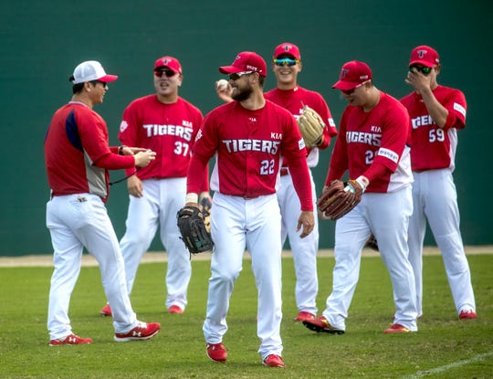 Preston Tucker, center, plays a fun game with teammates during a practice for the Kia Tigers, a South Korean professional baseball team. The team is spending Spring Training training at Terry Park in Fort Myers.
