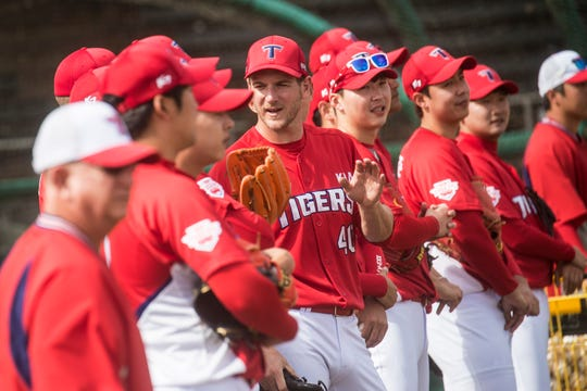 Drew Gagnon,  center, talks  with teammates during a practice for the Kia Tigers, a South Korean professional baseball team. The team is spending Spring Training training at Terry Park in Fort Myers.