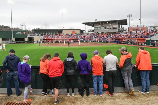 Clemson fans watch from the outfield fence during the top of the fifth inning of the home opening game with Western Carolina at Clemson Softball Stadium in Clemson February 12, 2020.