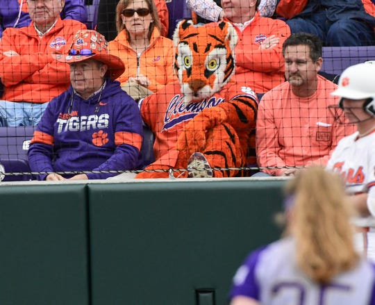 """Dean """"The Hat"""" Cox sits next to the Tiger Mascot during the bottom of the fourth inning at Clemson Softball Stadium in Clemson February 12, 2020."""