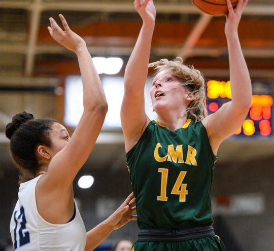 CMR's Allie Olsen attempts a shot over Great Falls High's Alison Harris during Tuesday's crosstown basketball game in the Swarthout Fieldhouse.