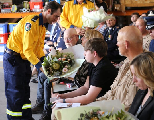 A  firefighter gives flowers to Dowdie McBeth, wife of Ian McBeth, during a Jan. 30 memorial in Richmond, Australia. Ian McBeth, Paul Clyde Hudson and Rick A. DeMorgan Jr., died when their C-130 Hercules tanker crashed Jan. 23 while fighting wildfires in Australia