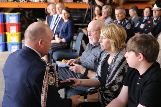 Dowdie McBeth, wife of Ian McBeth, is given her husband's commemoration from RFS Commissioner Shane Fitzsimmons, left, during a Jan. 30 memorial in Richmond, Australia, that also honored Paul Clyde Hudson and Rick A. DeMorgan Jr. They  died when their C-130 Hercules tanker crashed while fighting wildfires in Australia.