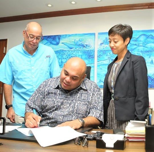 Guam Director of the Department of Labor David Dell'Isola and Sen. Régine Biscoe Lee look on as Acting Gov. Joshua Tenorio signs a worker's compensation bill into law.