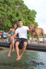 William Naden and Leilani Sablan with Naden's dogs, Koba, left, and Max, on Feb. 4, 2020, at the Merizo Pier.