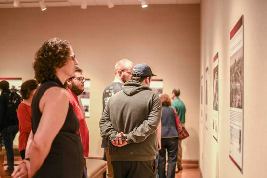 """People look at pieces in the """"Shoah"""" exhibit during its opening night featured in the Lucile Parker Gallery at William Carey University in Hattiesburg, Miss., Feb. 11, 2020"""