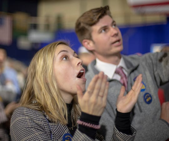 Ashley Guzik, left, and fellow college student Kyle McLellan, both from San Diego, watch the early returns for the New Hampshire primary at a Pete Buttigieg primary watch party at Nashua Community College in Nashua, New Hampshire, on Feb. 11, 2020. Early results showed Vermont Sen. Bernie Sanders in the lead.