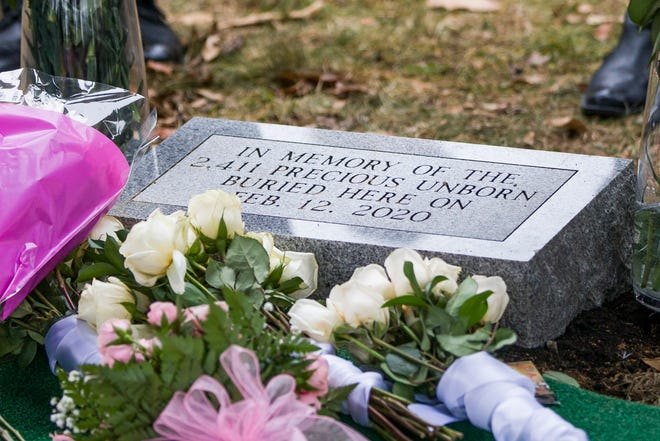 A grave marker is unveiled during a burial service, Feb. 12, at Southlawn Cemetery in South Bend, Indiana, for the more than 2,400 fetal remains found at the home of an abortion doctor.