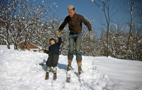 Bob Vollmer skiing with one of his young children. Vollmer just retired as Indiana's oldest state employee at 102 as a surveyor from the Department of Natural Resources.