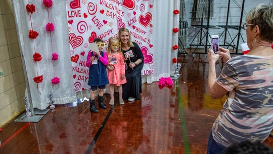 Kathi Bordlee takes a picture of (left) Jayda Judice, Madison Bordlee, and Jessica Bordlee at a Valentine's Day Sweetheart Dance at the Truman Early Childhood Education Center Tuesday, Feb. 11, 2020.