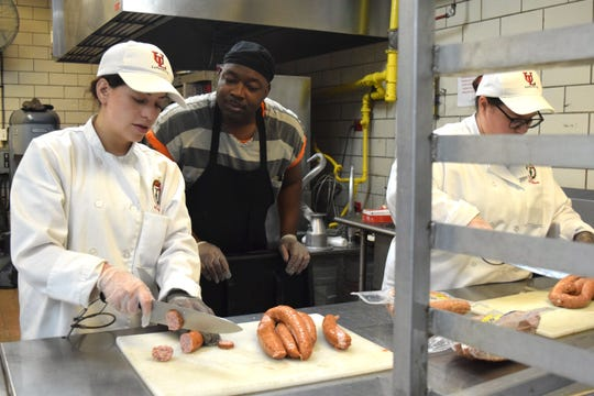 University of Louisiana at Lafayette students Kelu Archbold, left, and Kaylin Miller, right, listen as Chad Williams, a head chef inmate at the Lafayette Parish Correctional Center, gives directions in the jail's kitchen. Archbold and Miller are both seniors in the hospital management program and are completing their internship at the correctional center.