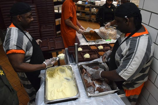 Chad Williams, left, and Duquean Lewis help prepare lunch trays that will be delivered to those incarcerated at the Lafayette Parish Correctional Center. Williams and Lewis are two of the main cooks in the jail's kitchen and are working with student interns from the University of Louisiana at Lafayette.