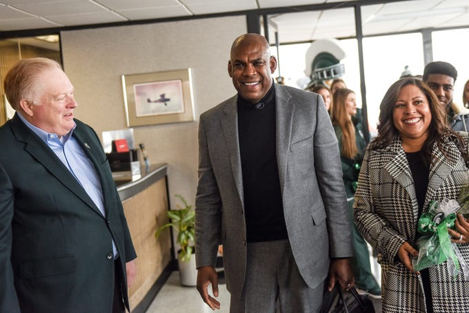 Michigan State's new head football coach Mel Tucker, center, and his wife Jo-Ellyn, right, talk with MSU Athletic Director Bill Beekman, left, on Wednesday, Feb. 12, 2020, at the Capital Region International Airport in Lansing.