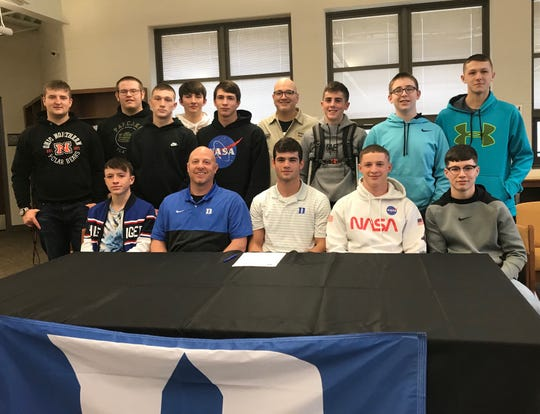 Conor Becker, a 2019 state champion, is seated next to head coach Scott Carr and surrounded by the rest of Northmor's wrestling team after signing a national letter of intent to attend Duke University.