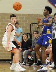 Ontario High School's Shaquan Coburn (11) makes a pass around Ashland High School's Grayson Steury (24) during a boys basketball game at Arrow Arena Tuesday, Feb. 11, 2020.