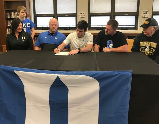 Northmor state wrestling champion Conor Becker signs his national letter of intent to attend Duke as coach Scott Carr and family looks on, including mom, Anna, and dad, Michael.