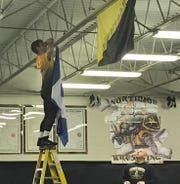 Northmor state wrestling champ Conor Becker hangs a Duke banner from the ceiling of the practice room as coach Scott Carr looks on.