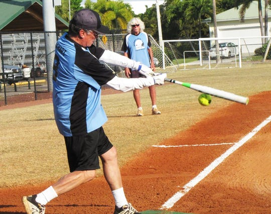 Bill Kayhart drives a hit down the third base line for the Snook Inn.