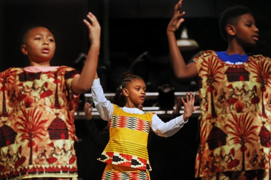 "Aaron Smith, 11, left,  Ni'Cyra Williams and Geno Cooks, 11, right, rehearse for ""We Are The Drum"" at Marshall High School on Wednesday, Feb. 5, 2020.  The cast members' costumes were flown in from Senegal for the performance."