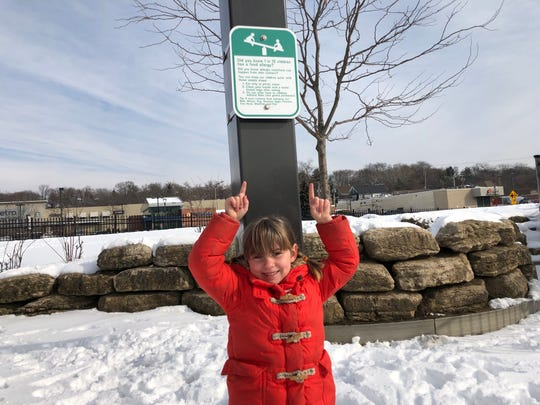 Six-year-old Iris Stroud stands below a new food allergen awareness sign that has been placed at Hark Park in Wauwatosa to warn others about how food allergies can impact people.
